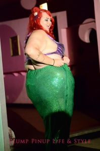 Photo: A fat white woman dressed as Ariel from The Little Mermaid with a purple seashell and green sequin tail. Google Images.
