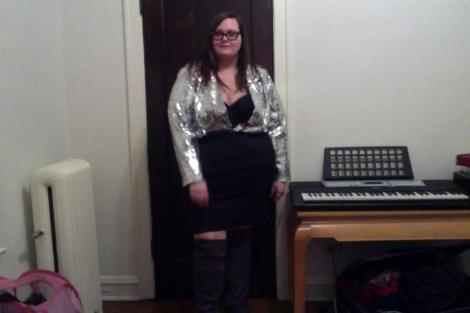 Photo: A fat white woman with long dark hair wearing a silver sequin top, black pencil skirt and dark grey thigh hi boots. Google Images
