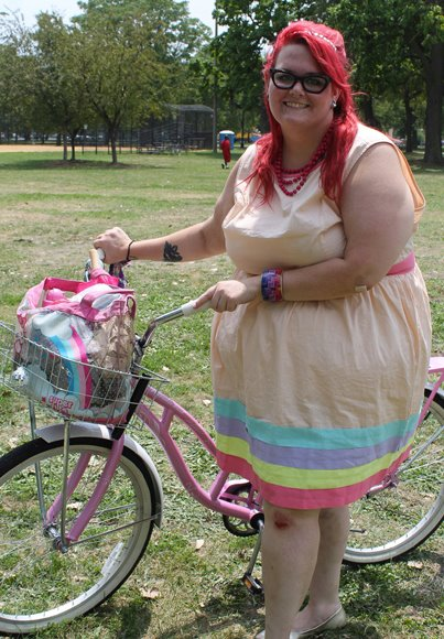 Photo: A fat white woman with dark pink hair in a peach dress with a rainbow hem and a pink bike. Google Images.