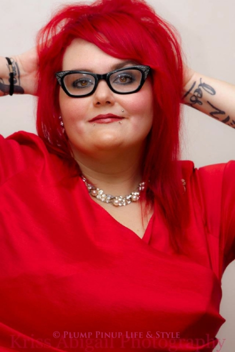 Photo: Headshot of a fat white queer femme woman with cateye glasses and red hair wearing a red dress. Photo source: Google Images, Kriss Abigail Photography