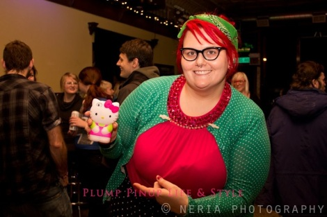Photo: The Lady Anita Butch, a fat white woman with red hair and cat eye glasses wearing a pink shirt, green cardigan with white polka dots and a black pencil skirt with white polka dots. Hello Kitty 3D iPhone case in pink and green. At Queer Amp at Quenchers. Photo source: Google Images, Jessica Neria Photography