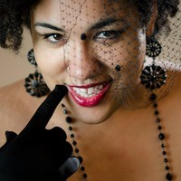 Photo: Jacqueline Boyd headshot, a queer woman of color wearing high femme fabulousness. Photo source: Google Images