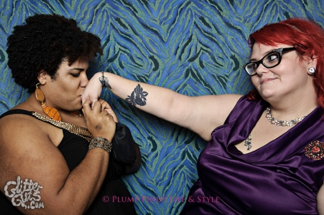 Photo: A fat black femme woman kisses the hand of a white fat femme woman with red hair at at Queerer Park: Homo for the Holidaze at Beauty Bar. Image source: Google Images, Glitter Guts